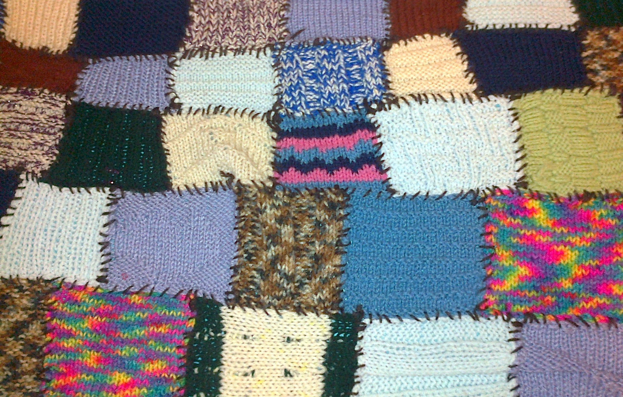 Blanket made by sewing together little knitted squares