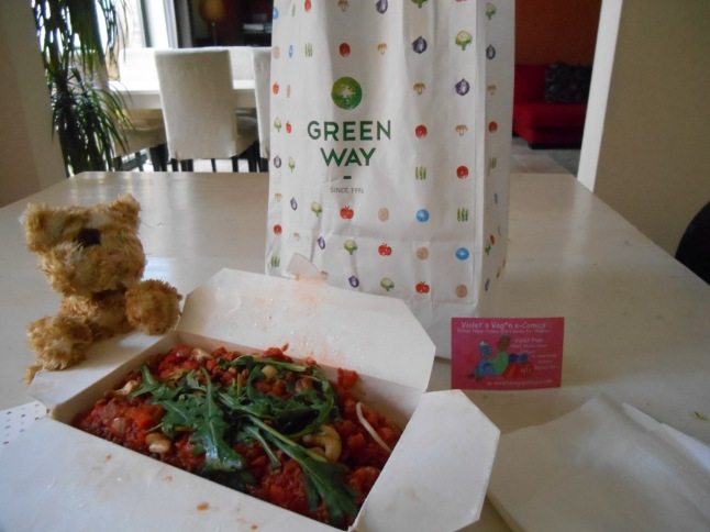 Take away food in paper bag from Greenway vegetarian restaurant.  Vegan Spaghetti bolognese.  In the cardboard box with a toy cat.